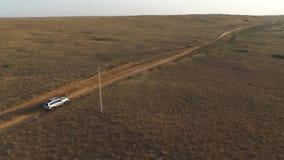 后面鸟瞰图:驾驶在日落前面的一个干草原的大银色SUV 影视素材