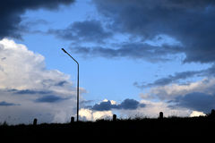 后面轻的灯岗位草甸和深蓝风雨如磐的多云天空在晚上 免版税库存照片