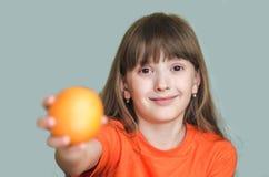 今后给桔子被伸出的胳膊的女孩 免版税图库摄影