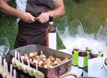 吐露一个瓶红葡萄酒的专业侍者 免版税库存图片