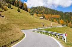 向一个五颜六色的森林的离开的弯曲道路 免版税库存照片