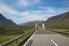 向一座桥梁的一条漫长的路有在高地惊人的风景的美好的山和小山视图 免版税图库摄影