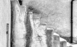 向上带领与一个简单的后边墙壁和排水设备管子的老石台阶 图库摄影