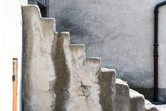 向上带领与一个简单的后边墙壁和排水设备管子的老石台阶 免版税库存图片