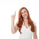 向上指向美丽的红头发人的妇女 库存照片