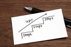 向上朝向与在纸的箭头的手写台阶 企业成功概念和成长想法 库存图片