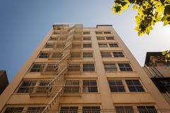 向上看与非常长的防火梯的一个城市大厦 库存图片