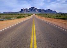 向原野的沙漠主导的山路 免版税库存图片