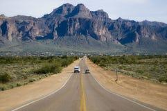 向原野的沙漠主导的山路 库存照片