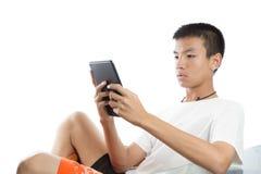 向后倾斜和使用他的片剂的亚裔少年 免版税库存图片