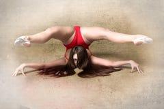 向后弯曲在难看的东西背景的年轻女性柔术表演者 图库摄影