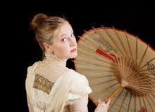 向后看与中国伞的维多利亚女王时代的礼服的女孩 免版税库存图片