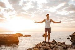 向后站立与胳膊的运动员上升了在多岩石的海滩 图库摄影