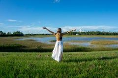 向后站立在一个美好的领域风景的白肤金发的少妇户外与培养手胳膊对天空 免版税图库摄影