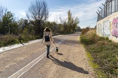 向后走和走与她的法国牛头犬狗的妇女 库存照片