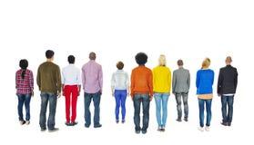 向后面对小组不同种族的五颜六色的人民 免版税库存照片