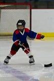 向后滑冰的男孩,当实践冰球时 免版税库存图片