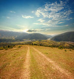 向土坎的乡下公路在晴朗的天空背景  库存图片