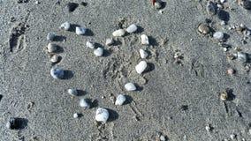 向在海滩的心脏扔石头 免版税库存图片