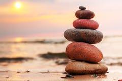 向在象征和谐的沙子的金字塔扔石头 免版税库存照片