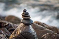 向在象征稳定,和谐,平衡的Pebble海滩的金字塔扔石头 浅深度的域 库存图片
