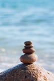 向在象征稳定,和谐,平衡的Pebble海滩的金字塔扔石头 浅深度的域 免版税库存图片