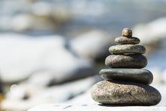 向在象征稳定,禅宗,和谐,平衡的Pebble海滩的金字塔扔石头 库存照片