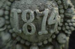 向在19世纪大厦的被雕刻的年建筑细节扔石头 图库摄影