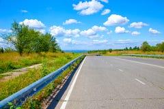 向天空和云彩的路 免版税库存照片