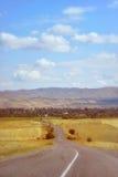 向山的一条漫长的路在领域中 库存图片