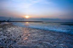 向日落海浪风车扔石头 免版税库存图片