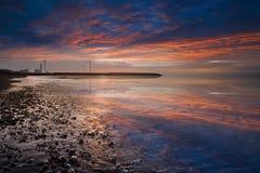 向日落海浪风车扔石头 库存照片
