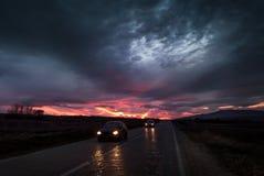向日落的直路接近与汽车通过的微明 免版税图库摄影