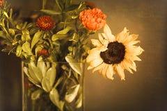 向日葵和橙色妈咪花束玻璃花瓶的在织地不很细金布朗墙壁前面 免版税库存照片
