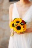 向日葵婚姻的新娘花束在新娘的手上 库存图片