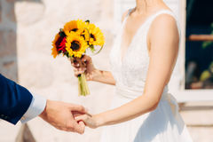 向日葵婚姻的新娘花束在新娘的手上 免版税库存照片