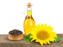 向日葵油、种子和花在木桌上有白色背景 免版税库存图片