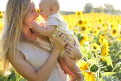 向日葵领域的愉快的母亲和小女儿 库存照片