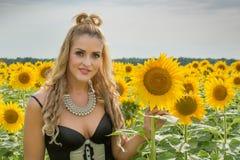 向日葵围拢的美丽的妇女 免版税图库摄影