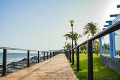 向有木栏杆的铺磁砖的海滩小径扔石头在夏天在白天 库存图片
