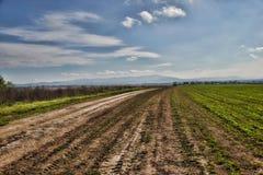 向村庄的土路 多云天空,斯洛伐克 免版税库存照片