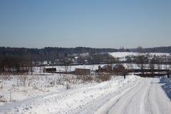 向村庄的雪道 免版税库存照片