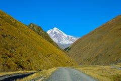 向村庄Sno,高加索山脉、山河、多雪的山峰Mkinvari和路的路 免版税图库摄影