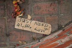 向标志行乞的无家可归的布朗袋子 免版税库存照片