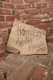 向标志行乞的无家可归的纸板 免版税库存照片
