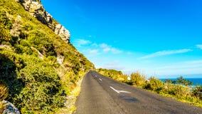 向沿街叫卖者` s峰顶的路沿在Slangkop灯塔的大西洋海岸 免版税库存照片
