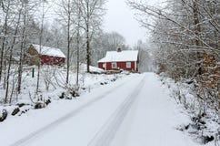向瑞典村庄的冬天路 免版税库存照片
