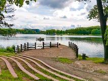 向码头的一条道路在有小船、多云天空和绿色树的湖 休息处,钓鱼 免版税库存照片