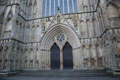 向被雕刻的入口扔石头到有雕象和曲拱的一个大教堂 免版税库存照片
