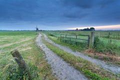 向风车的乡下地面路 图库摄影